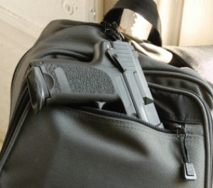 A black handgun rests part way in the front pocket of a black backpack