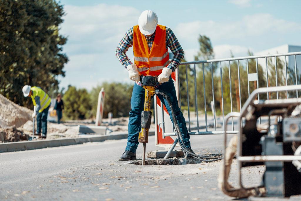 A male construction worker wearing an orange safety vest and white hardhat uses a jackhammer on an asphalt sidewalk