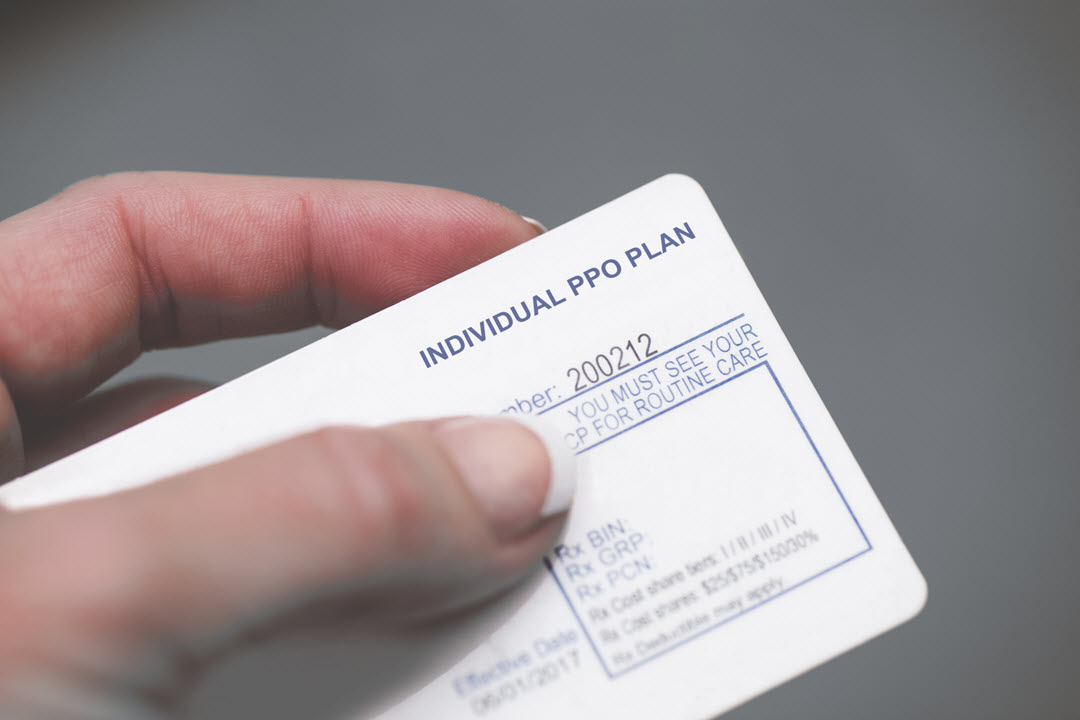 An insurance card is held between the thumb and index of what appears to be a female's hand. The nail of the thumb rests next to the group number of the Individual pro plan .