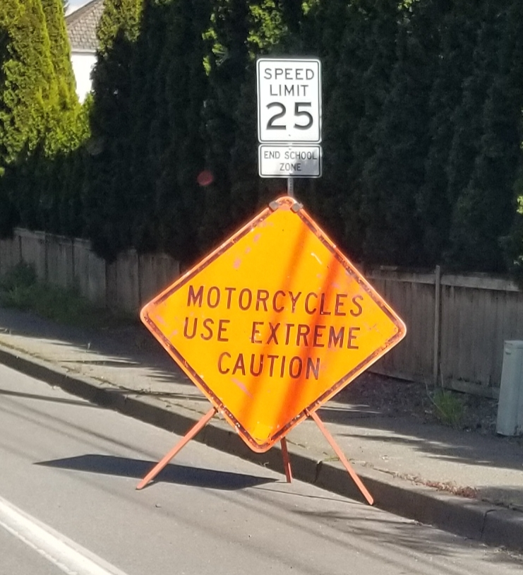 motorcycles use caution, road work sign,