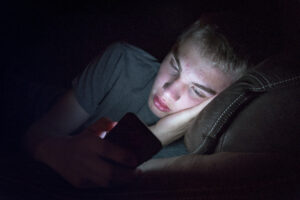 a teen lays down in the dark staring at his brightly lit smart phone