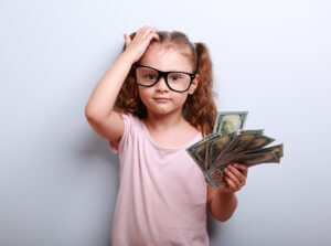 A female child holds a fanned out money with a confused look on her face