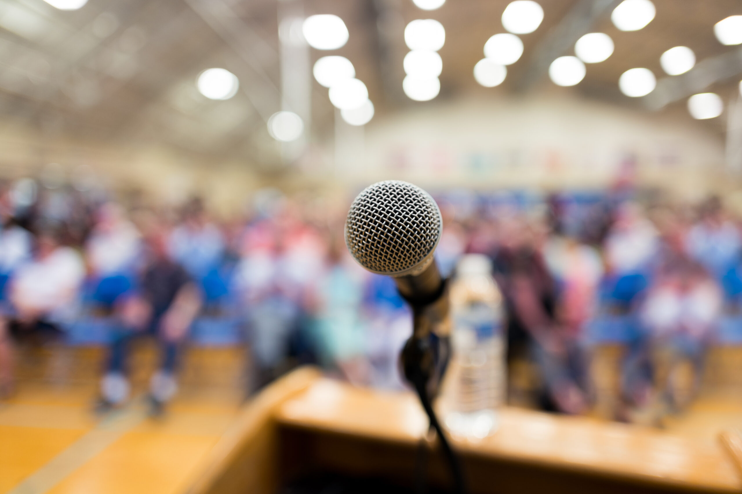 a microphone at a podium, the background a blurred audience