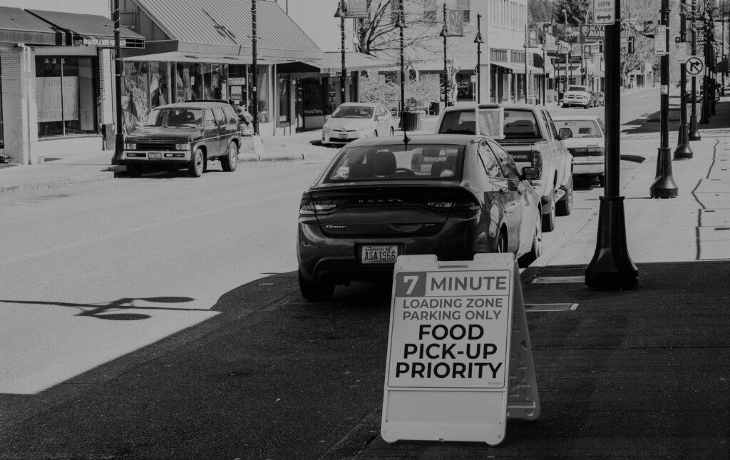 """A black and white photo of downtown E Main Street. The photo is taken from the sidewalk looking up toward Auburn Way South. On the sidewalk is a sign stating """"Food Pick Up Priority"""""""
