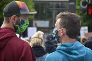 two adult males wearing face masks and hoodies look at each other during a large gathering outside of city hall.