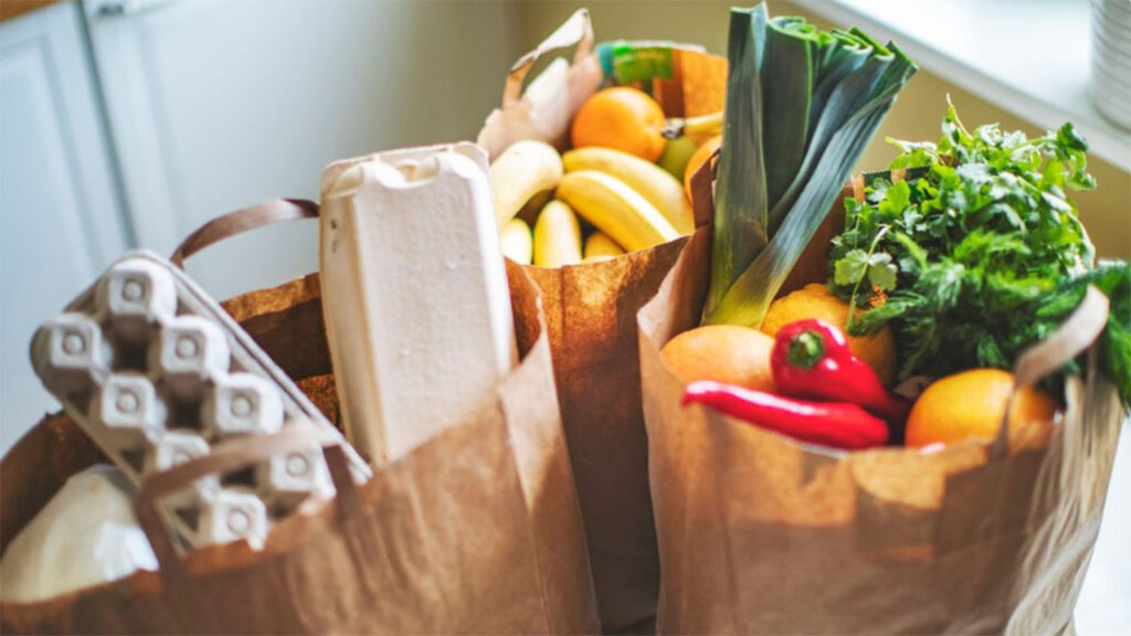 Three paper grocery bags full of colorful fruits, vegetables and other staple foods