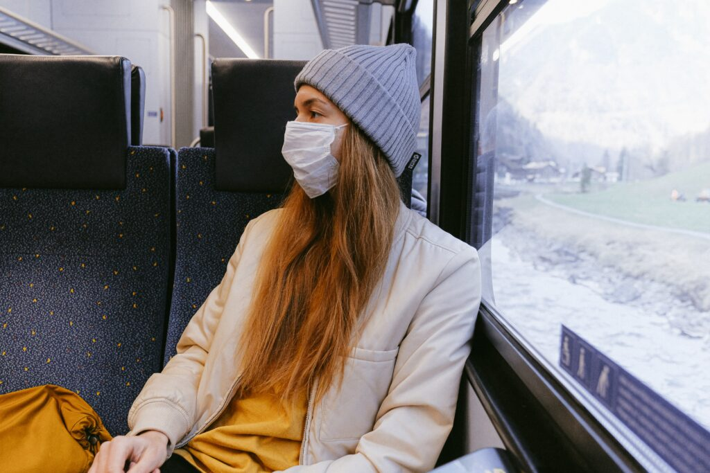 woman-in-gray-knit-cap-and-beige-coat-wearing a masks sits on a train with her back toward the window.