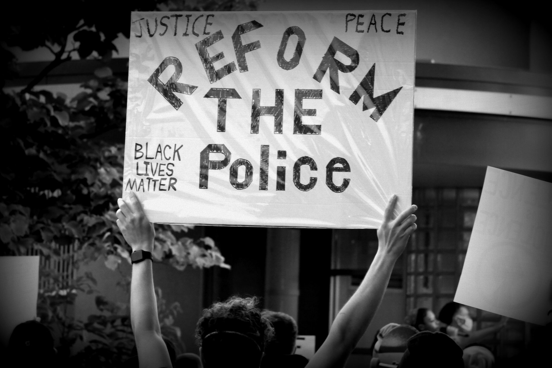 """A protester holds a sign during the June 2 BLM protest. The sign reads """"Reform the Police"""""""