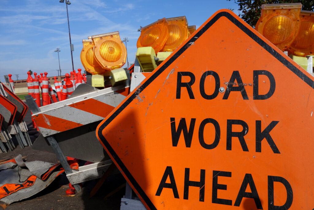 an orange road work ahead sign in front of stacked up temporary construction hurdles.