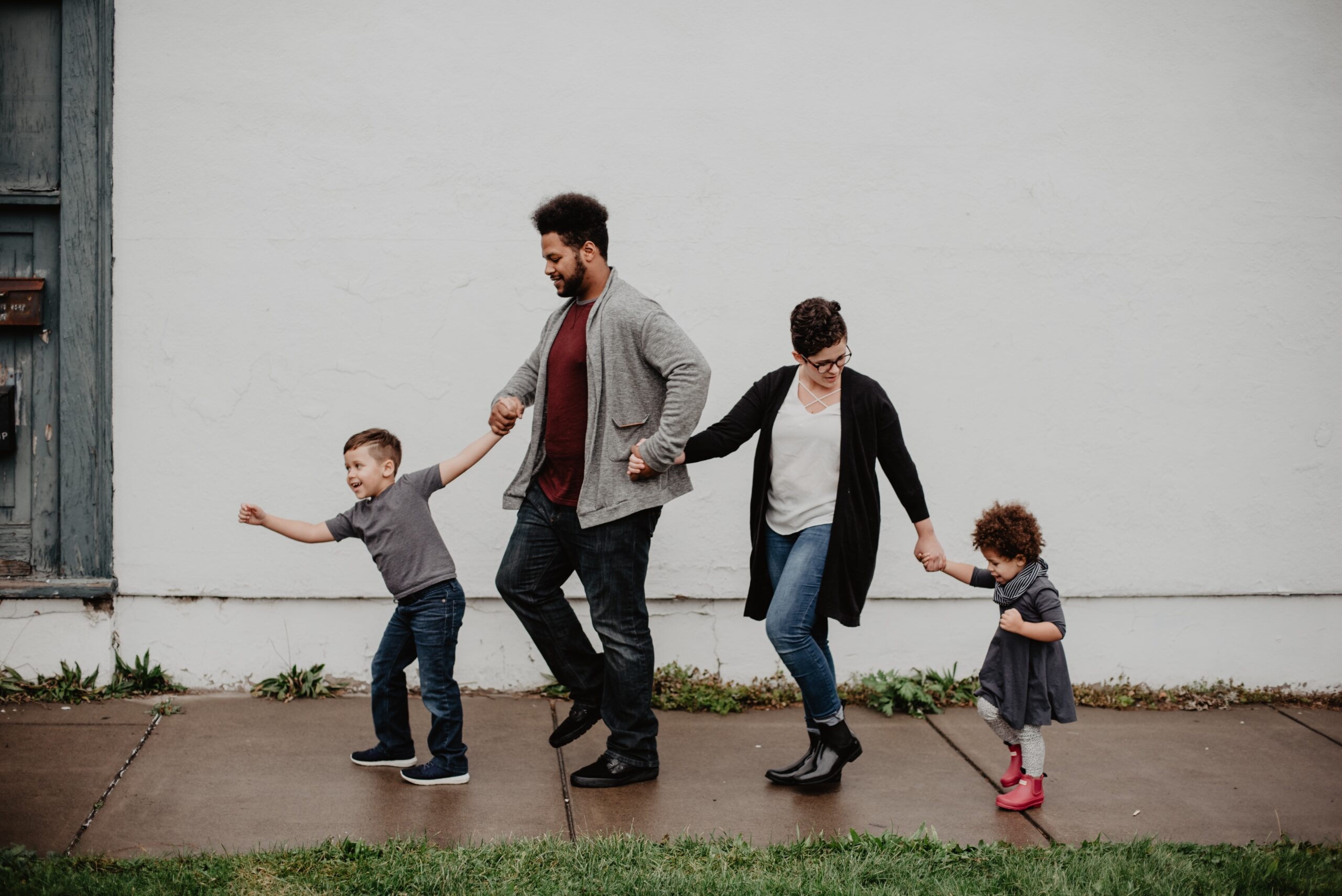 a family with two children walk in a line holding hands on a wet sidewalk