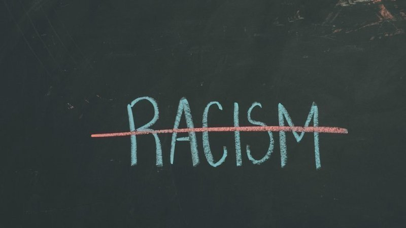"""The word """"racism"""" is written in light green chalk on a dark green chalk board and is crossed out with a red line."""
