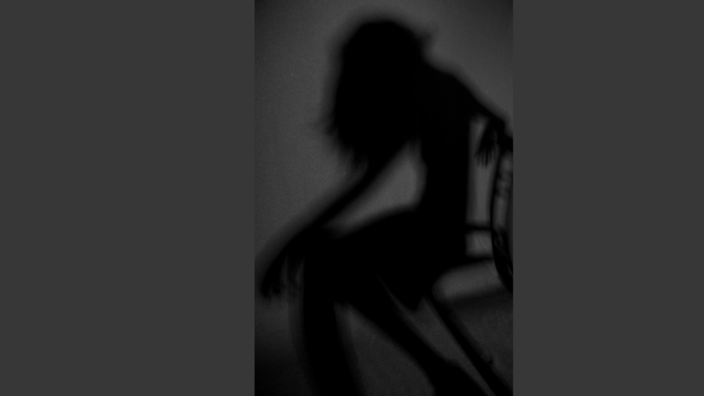 A shadow figure of a female sits forward and slightly hunched over on a chair. The background is differing hues of medium to dark gray.