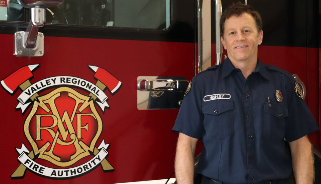 A photo of Valley Regional Fire Authority Firefighter Will Highley, a white middle-aged male with short brown hair wearing a dark navy VRFA uniform shirt with his name on the left side of his chest. He smiles as he stands in front of a VRFA fire truck.