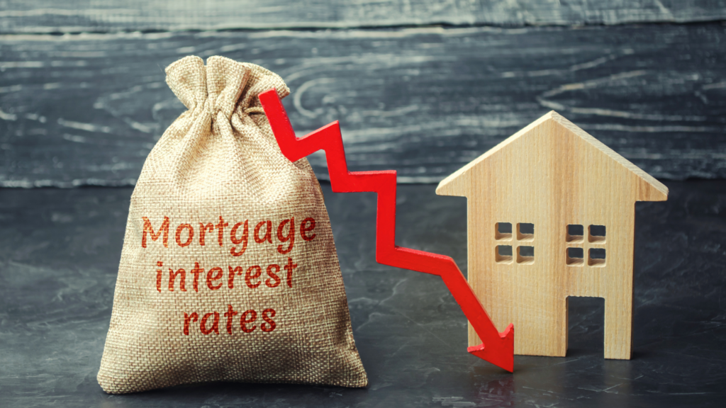 """A burlap sack sack with the words """"mortgage interest rates"""" sits to the left of a wooden block in the shape of a house. A red line with an arrow on the end starts at the top of the sack and points down toward the based of the house, with sharp ups and downs in it as it falls. The photo's background is a faded black and off-white wood panel."""