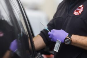 A hand wearing purple gloves holds a needle with the COVID-19 vaccine, a Band-Aid stuck to the back of their hand, the other hand reaches into an open car window.