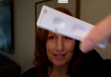 A white female, Congresswoman Kim Schrier, holds up a rectangular test.  The flat white plastic test has an open  oval space and an rectangle slot on it's front.