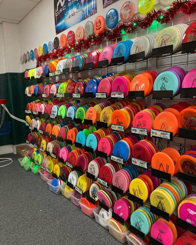 A colorful wall of Dic Golf disc plastics in the Mando's pro shop