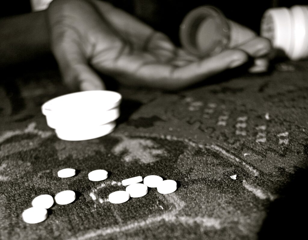 A cluster of white pills is focused in the foreground, a white pill bottle top is flipped on its side, a hand rests in the background, cupped with two pill bottles resting on its edge poised to pour.