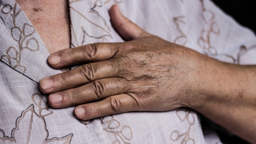 The hand of an elderly Black woman rests on her chest, over her heart. She wears a pale brown shirt with a tan design.
