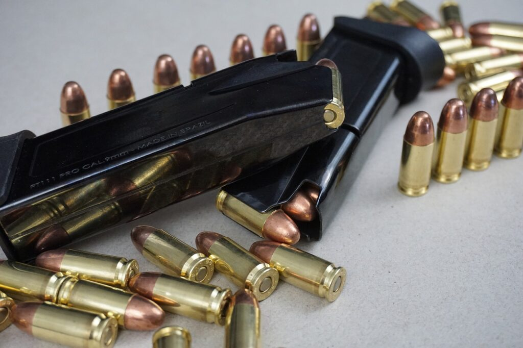 Two black, loaded, pistol magazines lay on their sides surrounded by a handful of loose bullets. The gold and copper unspent bullets in varying positions from from standing in a straight line, and laying in a pile.