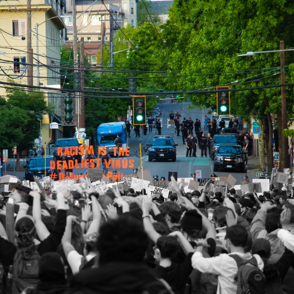 """Protesters gather in Seattle, carrying signs and banners. In the distance a group of Seattle PD officers and cars are seen blocking the road. The image is split, with the protesters being in black and white and the police being in color. One banner reads """"racism is the deadliest virus"""""""