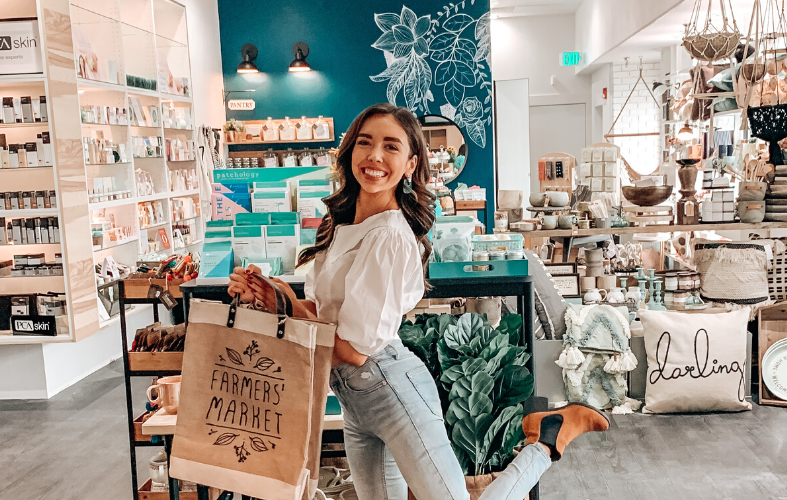 """A brunette female holds a burlap and tan style market bag with """"Farmer's Market"""" on it. She smiles as she kicks up one leg. The girl is in a well lit store with personal care, spa, and home items."""