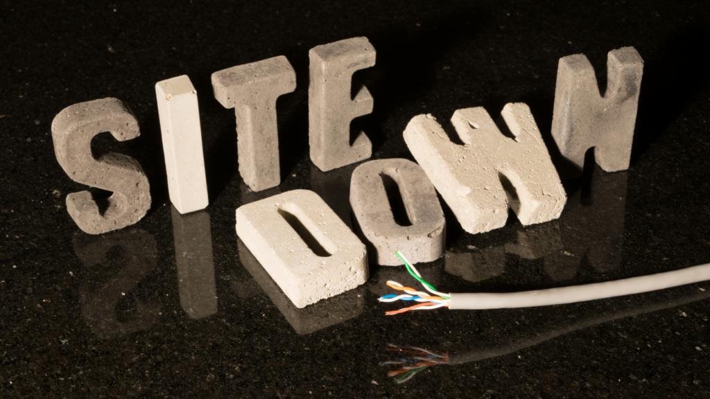 """White stone letters on a reflective black top say """"site down"""" The Down are fallen, with a cut cable laying in front of it."""