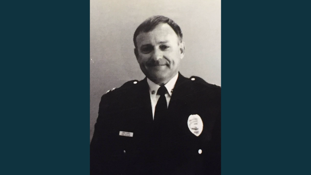 A black and white photo of man in a dress police uniform.