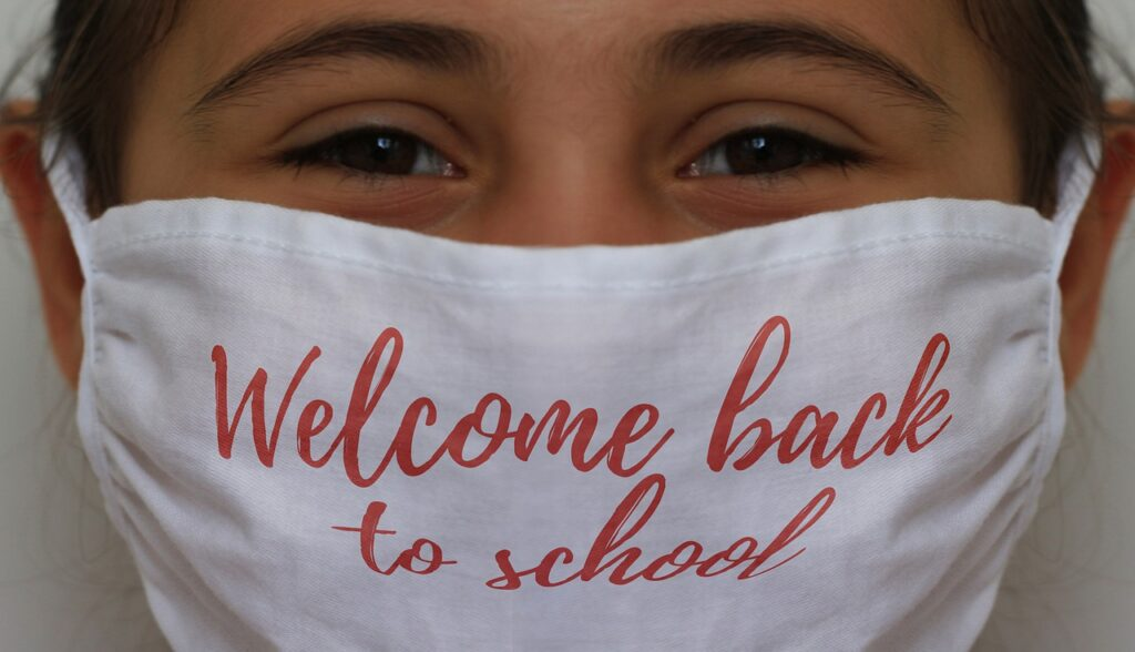 """A young girl smiles beneath a mask, her dark brown eyes and wisps of her dark hair the only parts of her face we see. Her white mask has """"Welcome back to school"""" written on it in red loopy letters."""