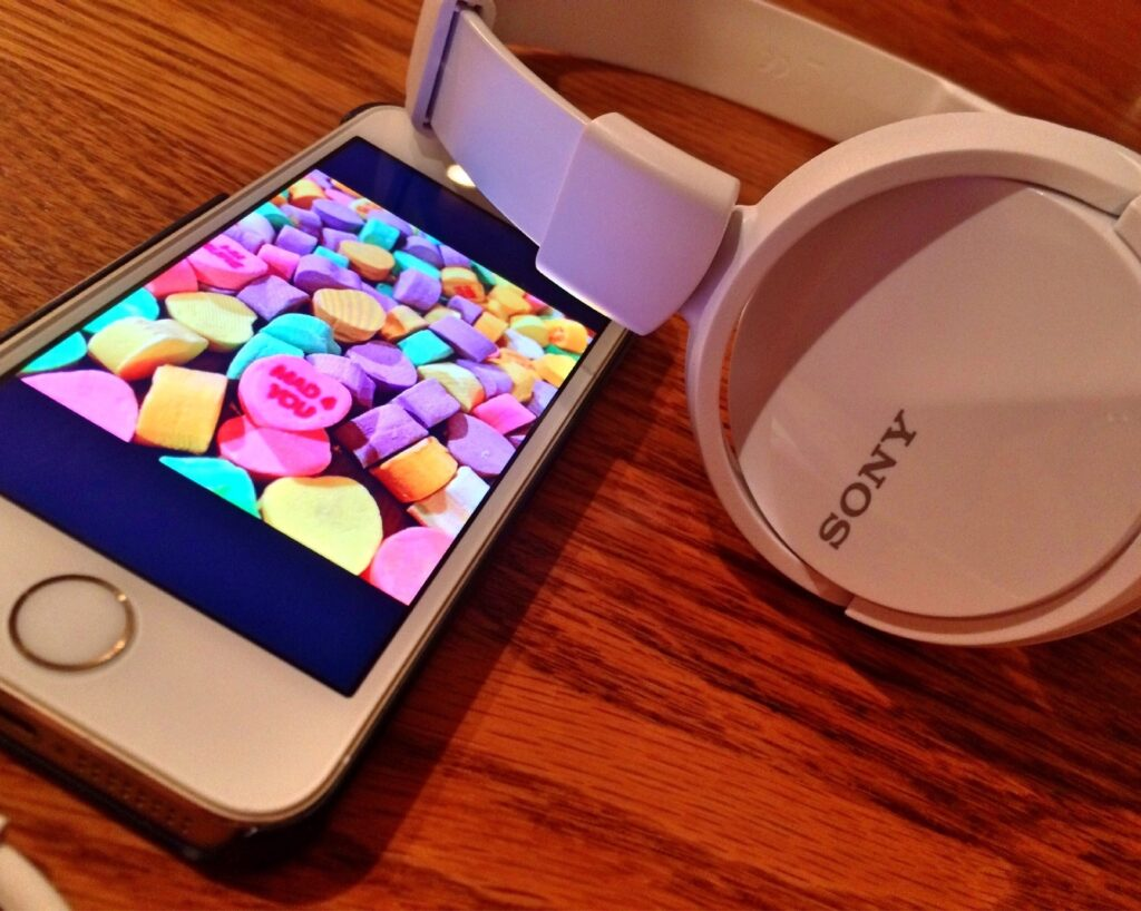 a white cell phone and sony pair of large round headphones sit on a wood tabletop. On the screen of the iPhone are colorful candy hearts.
