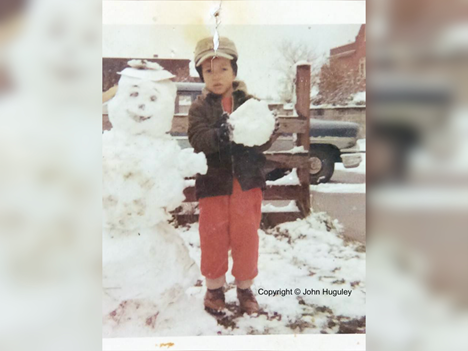 In an old photograph, a Black child stands next to a snowman that matches his size. He holds a large snowball. He wears a red jumpsuit and dark coat. A oversized winter hat tops his head.