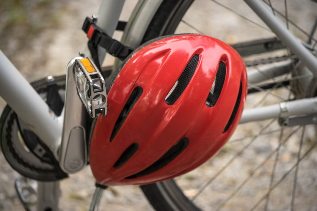 A red bike helmet is buckled around the middle of the bike.