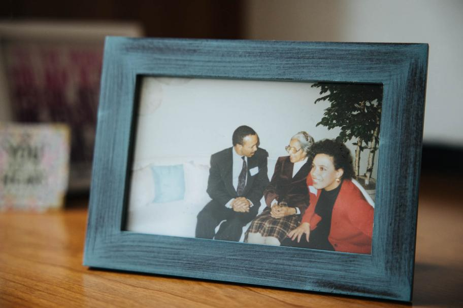 A rectangle photo in a thick black wooden frame sits on a wooden surface. The photo is of three African American individuals sitting on a couch, two women on the right and a man on the left.