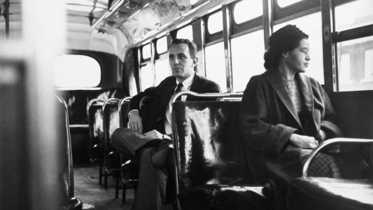A black and white photo of Rosa Parks, an African American woman wearing a long coat and round hat, sits on a public transit bus looking out the window. The bus is empty beyond a single white man in a suit that sits behind her.