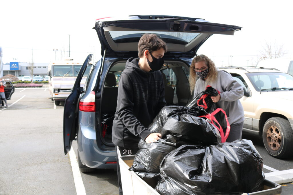 Alec Mayer and his mother, Donna Mayer unload large garabge bags full of donated socks into a wheeled laundry tote from the back of a minivan.