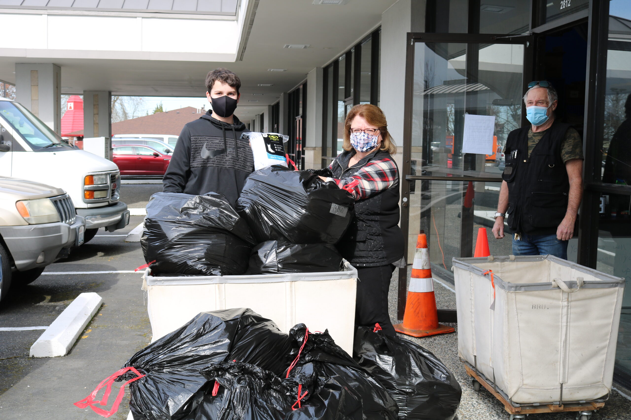 Boy Scout Alec Mayer stands next to Auburn Food Bank director Debbie Christian, before them a wheeled laundry tote overflowing with black garbage sacks full of socks