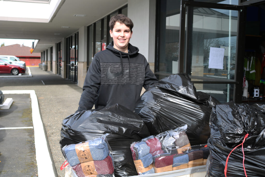 Boy Scout Alec Mayer stands in front of  a wheeled laundry tote overflowing with black garbage sacks full of socks.