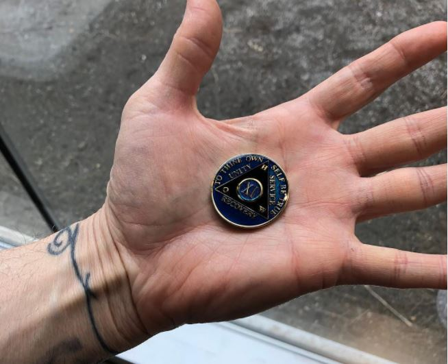 A person holds an 11 year AA sobriety token in the palm of their sprawled open hand. Their wrist has a thin black tattoo. olds an eleven year AA sobriety token in its palm. On the individual