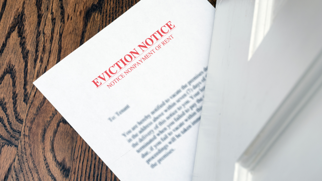 an eviction notice is slid under a white door