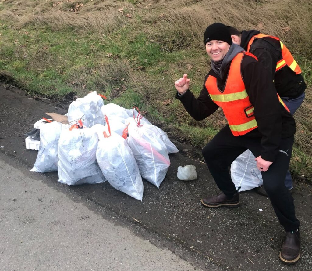"""Two adult males in orange safety vests stand next to a pile of full trash bags. The male in front is blocking the second male as he leans toward the pile of bags holding his hand up making a """"just a little"""" gesture with his hand."""