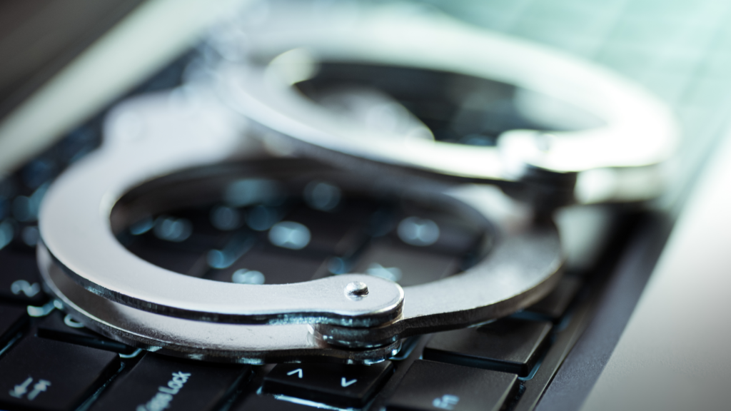 A pair of silver handcuffs on a black laptop keyboard