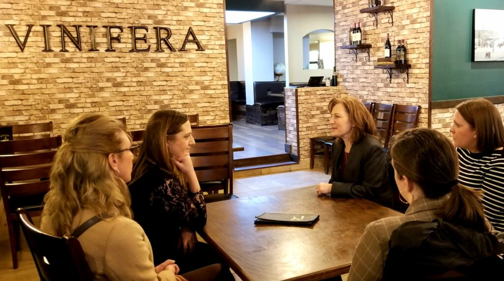 Rep. Kim Schrier and Brittiany Karlson sit across from each other at a table in Vinifera. They appear mid-conversation, with three other women listening