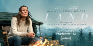 Robin Wright sits by a fire with a log cabin behind her in a mountain top setting on the movie poster for LAND