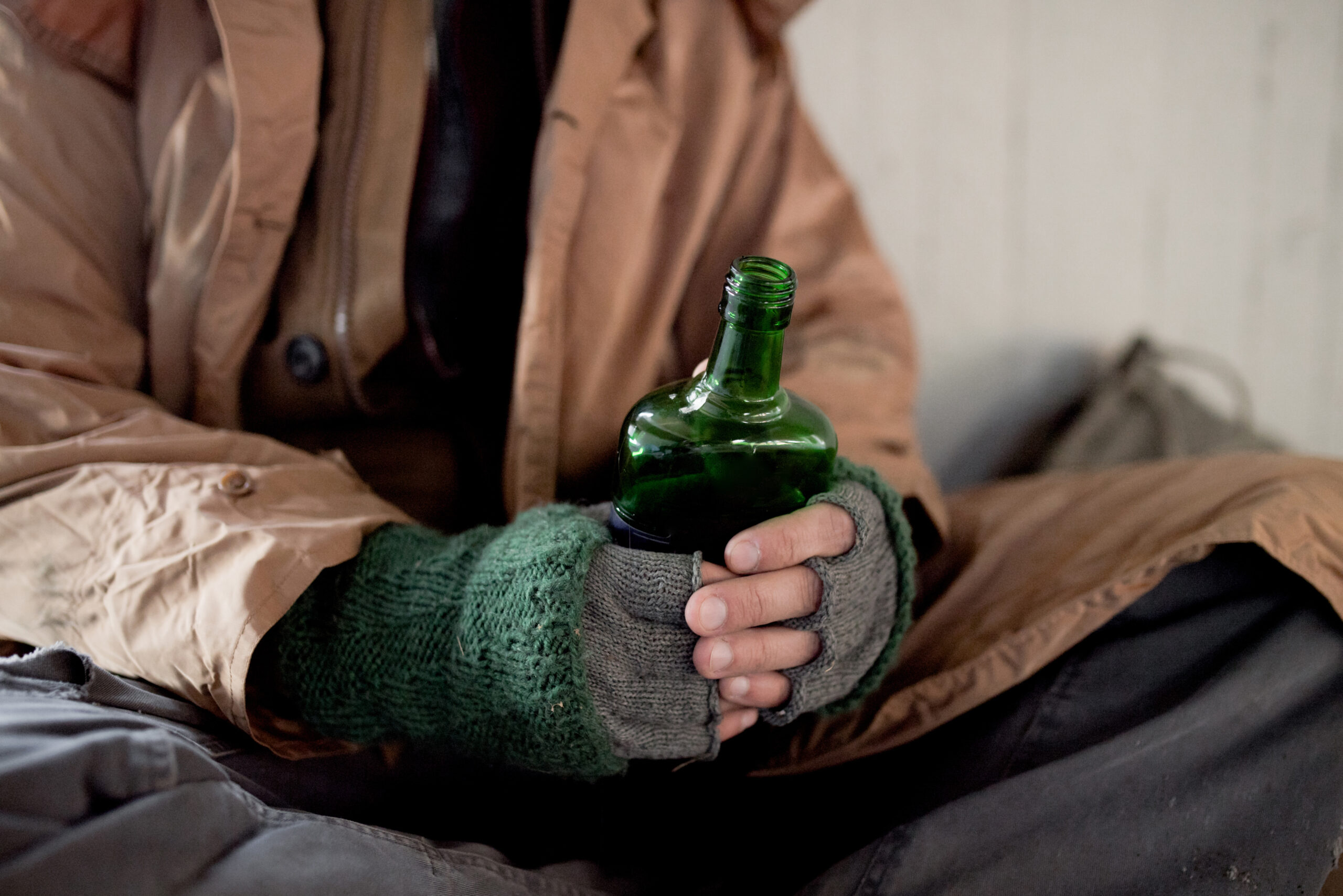 A midsection view of homeless man sitting outdoors in city asking for money donation, holding a bottle of alcohol.