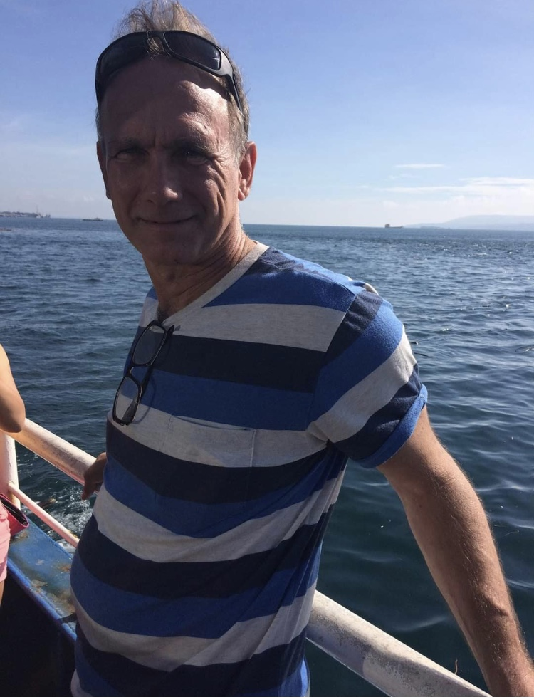 Ron Sorkness, a thing middle-aged white male with short light brown hair leans against a white metal rail. He wears a white, medium blue and dark blue striped shirt. Behind him is a large body of water that stretches to the horizon.