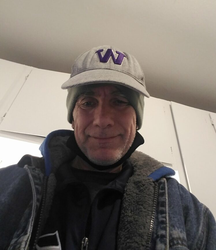 Ron Sorkness, a middle-aged white male, looks down at the camera while taking a 'selfie.' He wears a UW winter beanie that covers his ears and has a brim and a dark blue and charcoal coat.