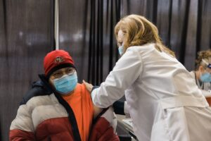 A female doctor in a mask, eye protection and a white lab coat administers an injection to a male in a neon orange t-shirt, gray and red puffy winter coat and SF 49ers beanie. The male wears a mask and glasses, his coat unzipped and partially pulled down his arm to allow for the injection.