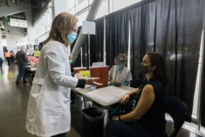 A female doctor in a white lab coat speaks to a female sitting in a chair. They are in