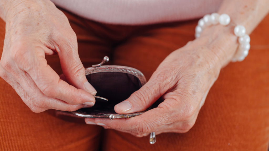 an older woman holds open a change purse on her lap. We see only her hands, with one putting a coin into the purse