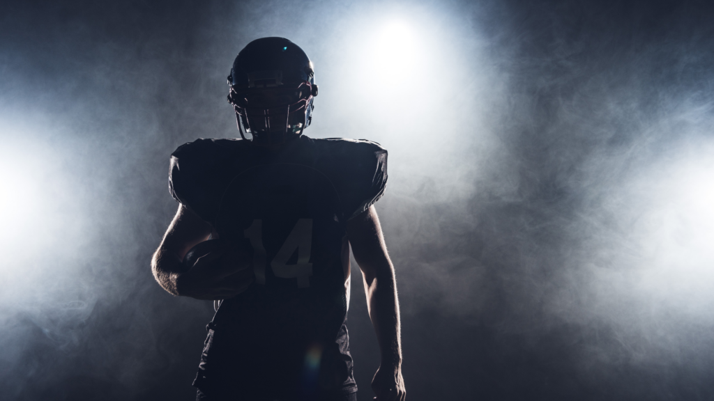 The silhouette of a football plater is surrounded in a thing smoke, shielding his features. He cradles a ball in his left arm.